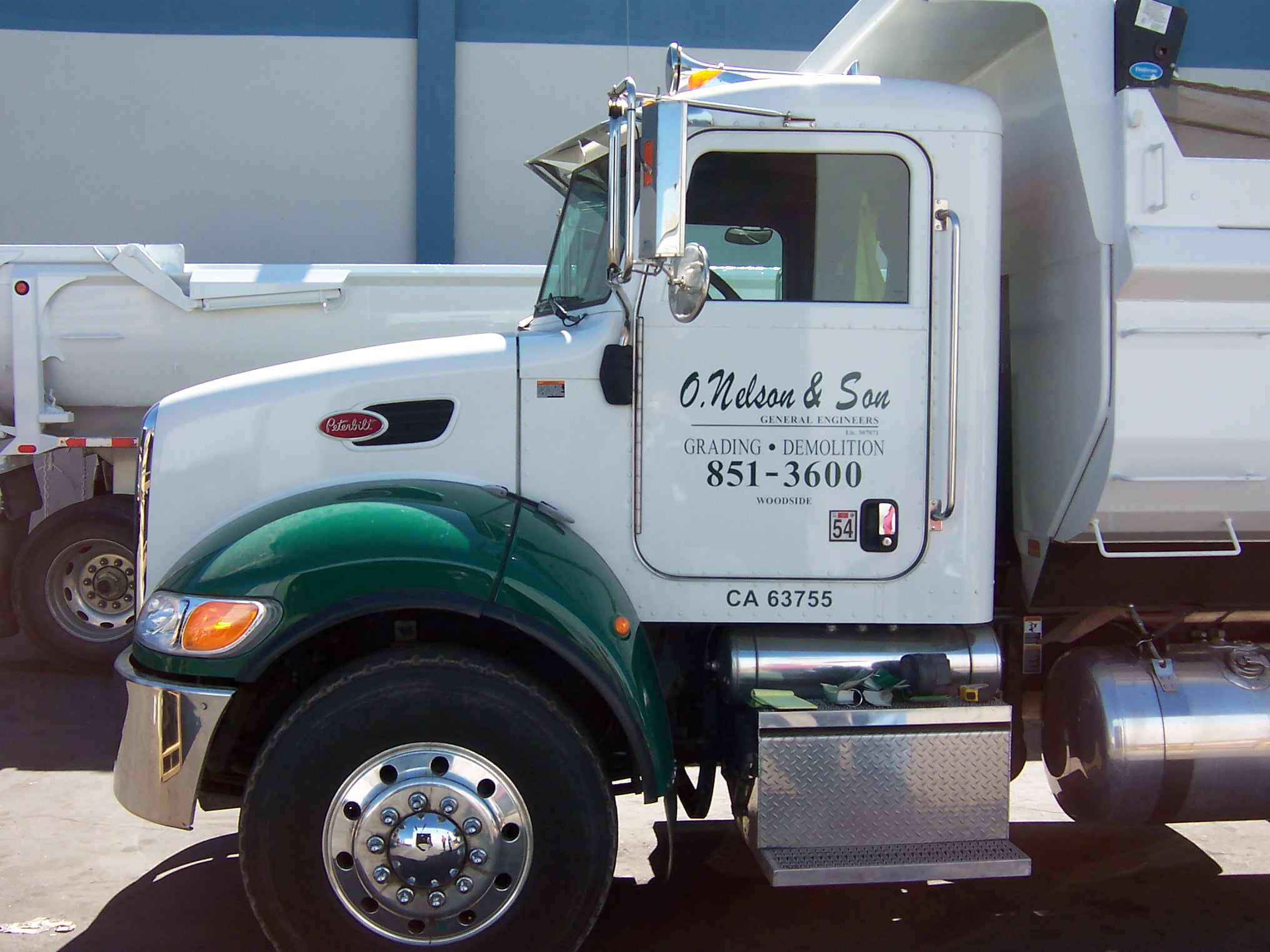 Heavy commercial truck with cab painted a two tone & doors with vinyl letters.